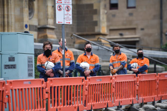 Workers listen to bugler Jason Reeve play the Last Post outside Flinders Street Station on Wednesday.