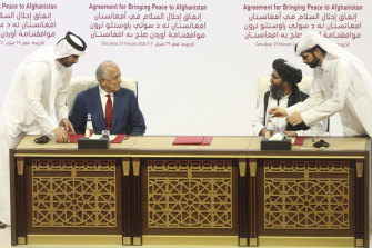 "US envoy Zalmay Khalilzad (left) and Taliban leader Abdul Ghani Baradar sign the ""Agreement for Bringing Peace to Afghanistan"" in the Qatari capital Doha."