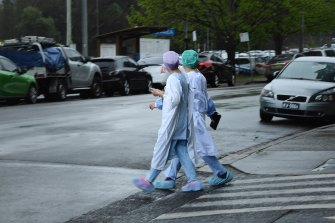 Health workers cross the road near Concord Repatriation General Hospital.