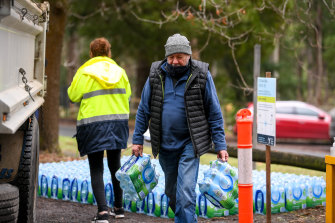 Kallista resident Jeff Seigerman carries bottles of water brought in for residents after they were warned not to drink water from their taps.