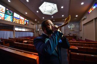 Rabbi Daniel Rabin blows a shofar in his Caulfield South synagogue.
