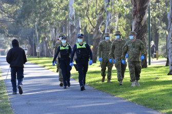 Victorian Police and ADF personnel patrol Princes Park in Carlton on Friday morning.