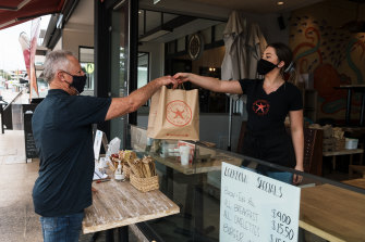 Greg Mullins takes delivery of his take away from Seachange Cafe in Dee Why.