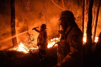 Volunteer firefighters work to keep a fire north of Batemans Bay from crossing the Kings Highway, in early January 2020.