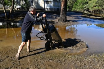 Russell Strickland  clearing mud from his cabin at Leetsvale Caravan Park along the Hawkesbury River.