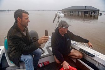 Dan Streat, left, video-calls Mario Fenech from a boat above Mr Fenech's turf farm.