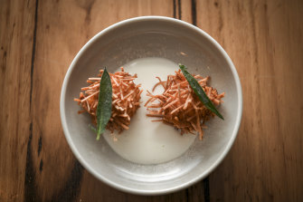 Angel-hair pasta croquette with pumpkin and emmental cheese rests on a moat of buffalo milk.