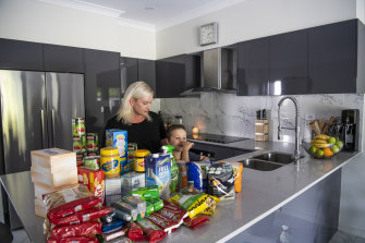 Julie Mason with her son Thomas in her Ermington kitchen with extra groceries.