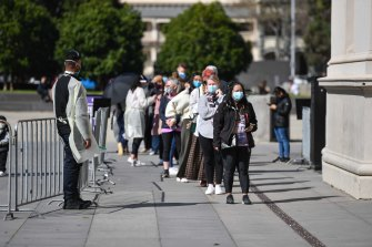 People queue to be vaccinated at the Royal Exhibition Building in Carlton at the weekend.