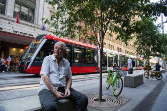 A tram passes Woolloomooloo resident Kenny Charles on George Street.