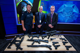 Assistant Commissioner Bob Hill, Detective Superintendent Peter Brigham (middle) and Detective Inspector Mick Daly with a cache of seized firearms