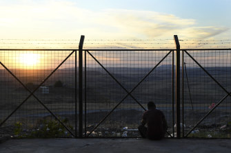 A refugee who has fled Syria into Iraqi Kurdistan looks towards his homeland as the sun sets on the holding centre for undocumented refugees.