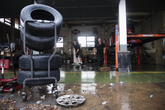 Workers at M&T Tyre Centre mop up after Wednesday's sudden inundation.