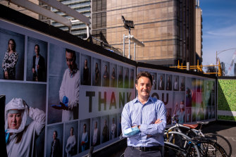 Dr Julian Druce, head of virus identification at the Doherty Institute, outside the Metro Tunnel hoardings where the photo gallery of health workers has been installed.