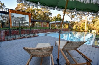 Luke Sheahan's Eltham home features a tennis court, decking with an infinity pool and an overhanging garden. Adjacent is a sunken lounge, spa, fire pit and a pool house along with a putting green.