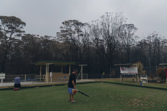 Residents of Lake Conjola help clean up the local bowling club, with burnt forrest just metres behind them.