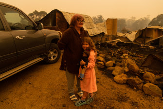 Barbara Rugendyke and her adopted daughter Sarah, who holds a doll, the only item she took with her when the family evacuated on Tuesday morning.