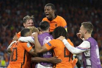 Netherlands players celebrate after Denzel Dumfries' late winner.