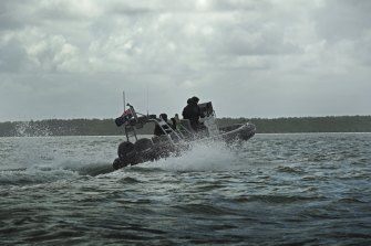 Australian Border Force (ABF) Marine Tactical Officers on a tender boat with the PNG coastline in the background.