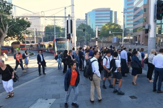 Pedestrians crowd onto a footpath between the light rail line and Elizabeth Street near Central Station.