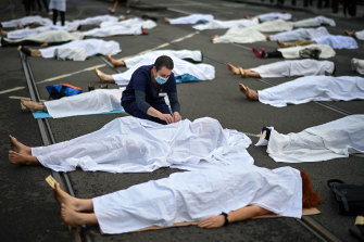 Some participants lay covered in white sheets.