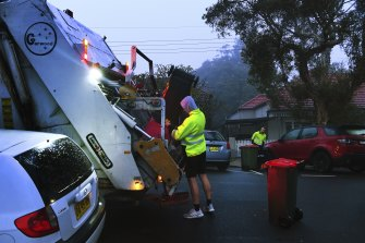 Men load rubbish into a truck that collects residential waste along Macauley street in Leichhardt.