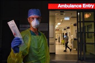 St Vincent's Hospital registered nurse Damien Davis Frank holding one of the new rapid testing swabs for COVID-19.
