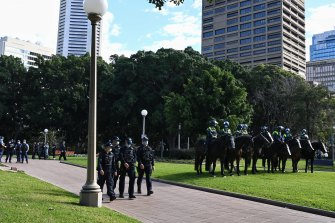 Police and mounted police wait in the empty Hyde Park.