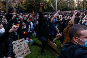 Thousands of protesters kneel and salute at a Black Lives Matter.