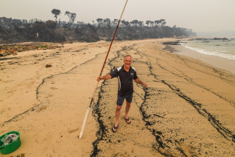 Fisherman Brett Mayor, from Melbourne, was the only person on the ash-covered beach.