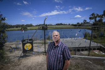 Dr Mark Glazebrook, from Friends of Lake Knox Sanctuary, stands in front of the fence that locals have covered in blue ribbons.