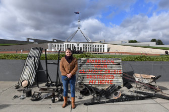 Melinda Plesman stands with the remains of her burn't out house outside Parliament House on Monday.