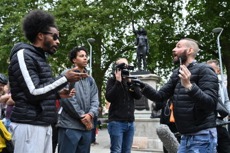 A man (right) argues against the new sculpture, by local artist Marc Quinn, of Black Lives Matter protester Jen Reid.