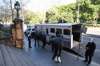 Police tend to their horses.