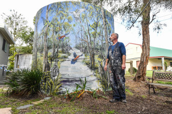 Artist Simon White with one of his murals, on a water tank, in Loch Sport.