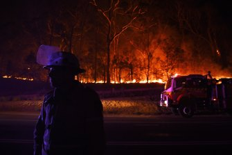 An RFS firefighter with the Charmhaven unit monitors a small flare-up on New Year's Day on the Kings Highway near Batemans Bay.