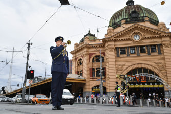 Bugler Jason Reeve plays the Last Post at the intersection of Flinders and Swanston streets on Wednesday.