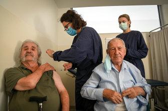 John Manolakakis and his father Jim Manolakakis receive a coronavirus vaccine at Altona North Respiratory Clinic on Monday morning, administered by nurses Peirrene McConville (left) and Chloe Coffin.