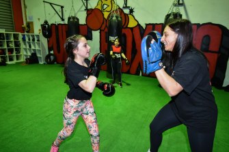 Tiahna, 12, trains with Samantha Holborn as her sister Aliyah, 10, watches on at Garside's home gym, Pure Boxing in Ringwood.