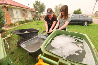 Clare  Morgan and her daughter Abbey  fill up bins and barrows with water to defend their home.