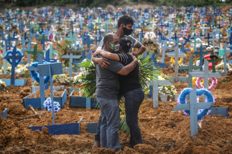 People mourn their relative at a Manaus cemetery where hundreds of COVID-19 victims have been buried.