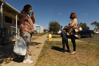 Members of the Boney family wait for other relatives outside the Ochre medical centre in Brewarina.