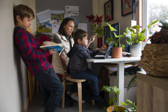 Dee Mills helping her sons, Jaxon, 9, and Harrison, 5, with their school work in their Matraville home.