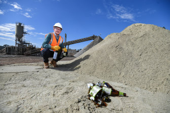 The firm's general manager recycling industries Mark Barraclough with glass bottles before and after being processed in a pile of sand.