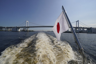 The Japanese flag flies from the stern of a cruise boat during a media tour of Tokyo Bay ahead of the start of the Summer Olympics on Monday.