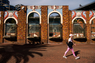 A pedestrian passes the art-deco brick wall that borders North Sydney Olympic Pool, on the edge of Sydney Harbour, on Tuesday.