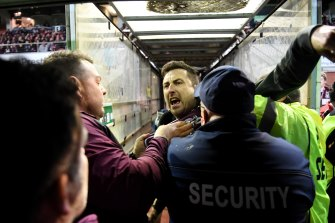 Security and police swooped on a Manly fan, centre, who confronted Melbourne Storm's Will Chambers.