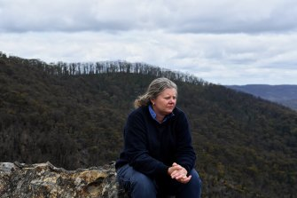 Mount Wilson RFS captain Beth Raines at Du Faurs Rocks lookout, with bushland in the background that was affected by the Mount Wilson backburn during the 2019/2020 bushfires.