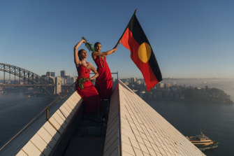 Abigail Delaney and Dubs Yunupingu from the Jannawi Dance Clan, from the Darug nation, flying the Aboriginal flag on top of the Opera House to promote Dance Rites, a celebration of First Nations dance.