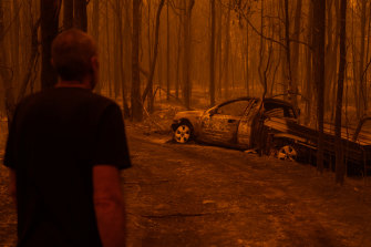Grant looks at the burnt car he tried to escape in.